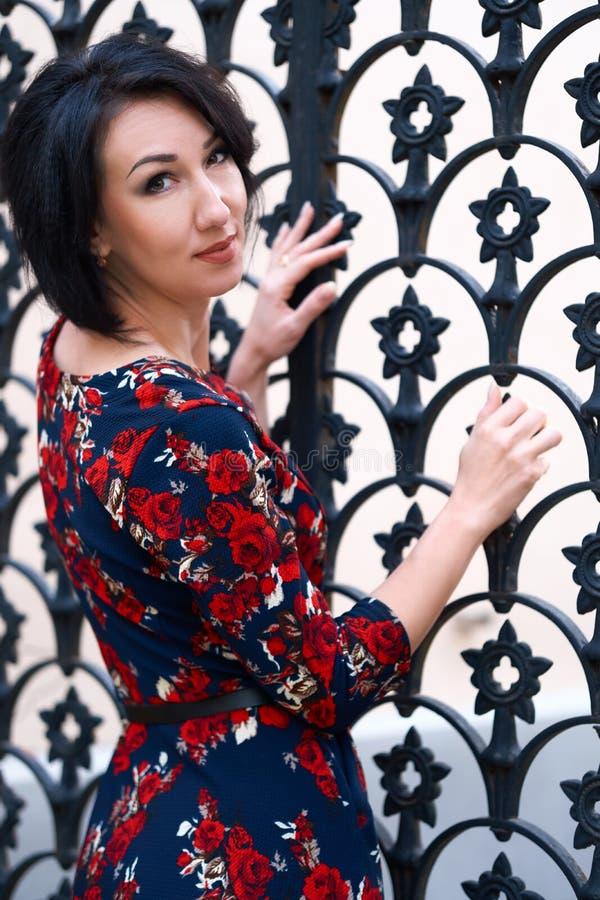 Beautiful elegant woman posing near black wrought iron gates royalty free stock images
