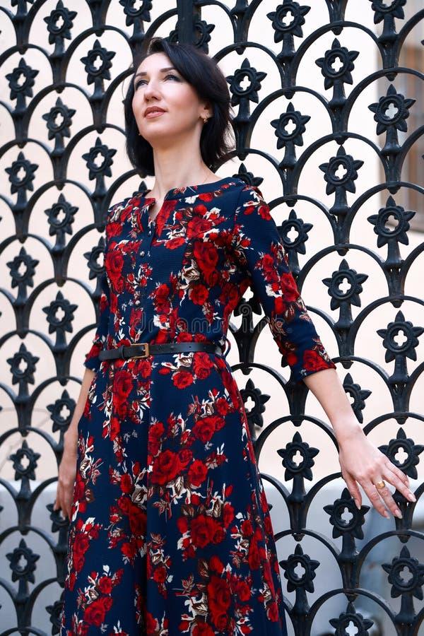 Beautiful elegant woman posing near black wrought iron gates royalty free stock image