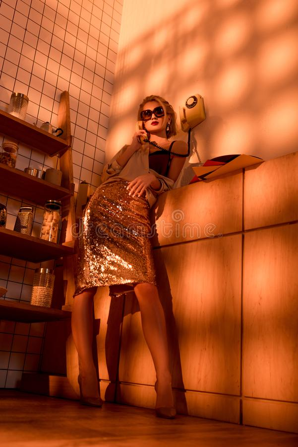 Beautiful elegant woman in sunglasses talking on retro telephone in kitchen. With orange light stock image