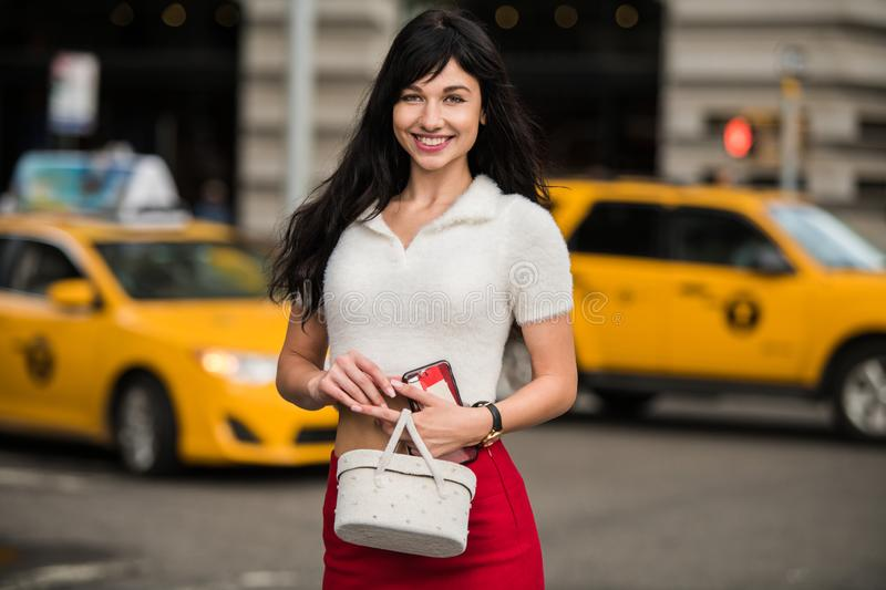 Beautiful elegant woman waiting for yellow taxi on city street of New York. stock photos