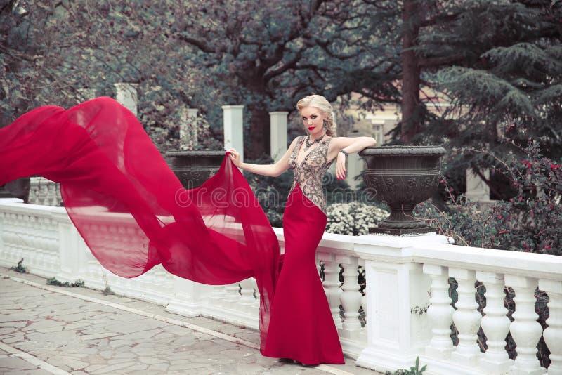 Beautiful elegant woman wearing in long mermaid fluttering fashion dress in winter park, outdoors full length portrait. stock photo