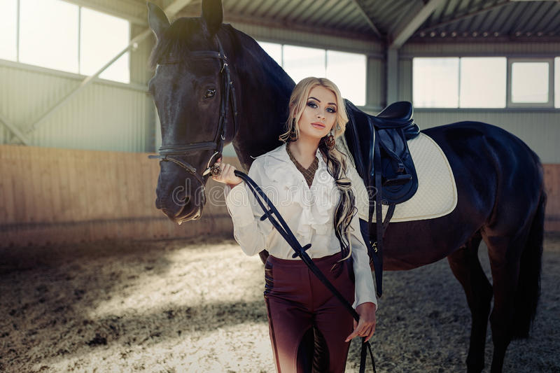 Beautiful elegant young blonde girl standing near her horse dressing uniform competition stock images