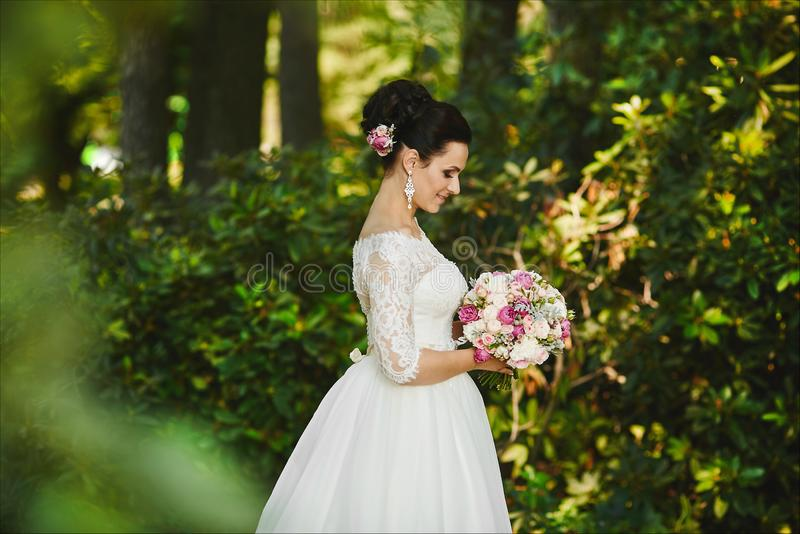 Beautiful and elegant young brunette woman with fashionable hairstyle in stylish wedding dress with a bouquet of white royalty free stock images