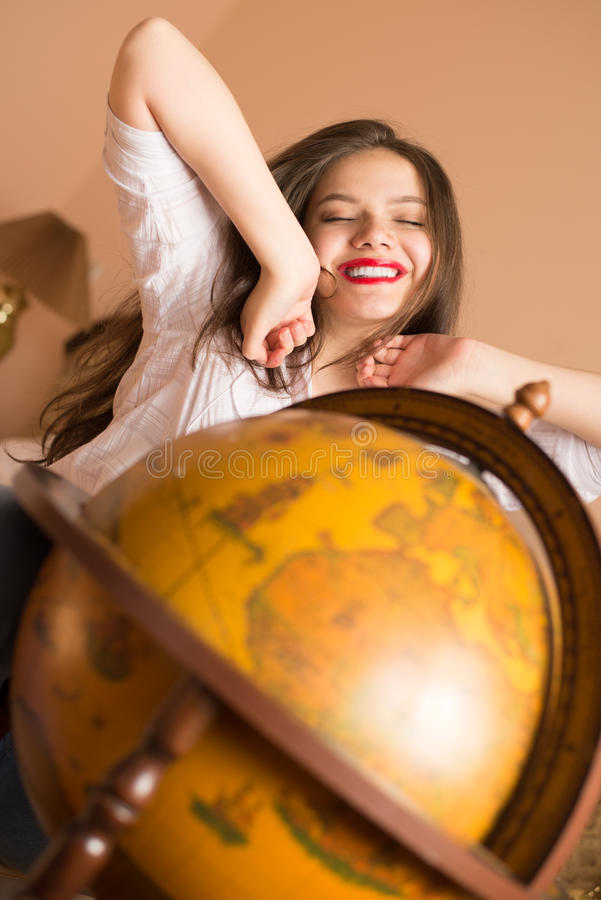 Beautiful elegant young woman attractive brunette female student happy smiling with red lipstick stretches at the globe royalty free stock photos