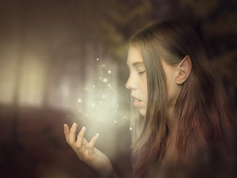 Beautiful elf girl portrait close-up in the forest looking at the glow on her hand. Fantasy photo art stock images