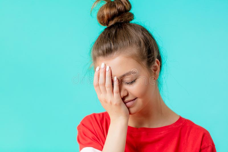 Beautiful embarrased woman covering with hand her eye. On blue background, close up portrait. shame, emotions, feelings concepts, female feels ashamed stock image