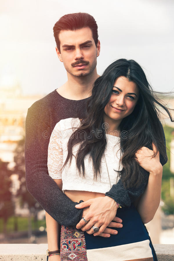 Beautiful embracing lovely young italian couple outdoors royalty free stock photos