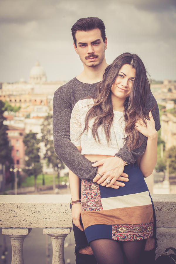 Beautiful embracing lovely young italian couple outdoors stock photo