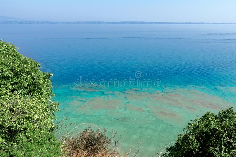 Beautiful emerald and calm waters of Lake Garda near Sirmione town, Italy. On the horizon in the fog the shore with small towns on. The lake stock photos