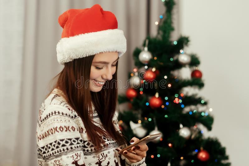 Beautiful emotional brunette woman in red santa hat and reindeer. Sweater texting on her smartphone while decoration christmas tree with colorful ornaments royalty free stock images