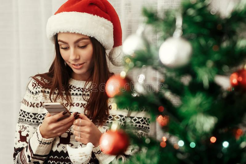 Beautiful emotional brunette woman in red santa hat and reindeer. Sweater texting on her smartphone while decoration christmas tree with colorful ornaments royalty free stock photography