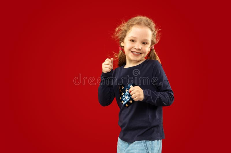 Beautiful emotional little girl isolated on red background royalty free stock images
