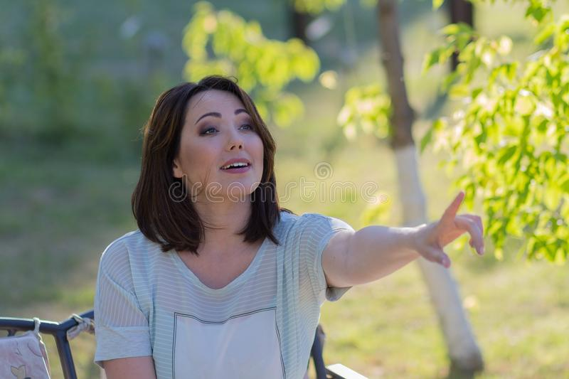 Beautiful emotional woman points finger sitting on the bench stock photography