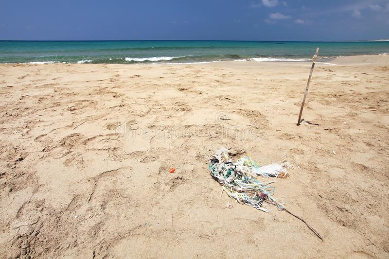 Beautiful empty beach, small pile of rubbish tangled plastic ropes on fine sand. Ocean littering concept. Karpass, Northern. Cyprus royalty free stock photo