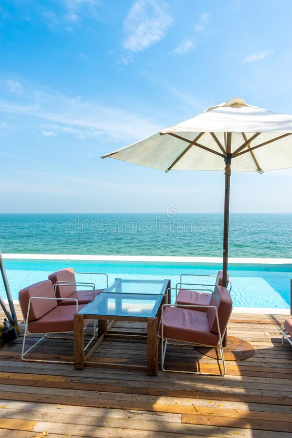 Beautiful And Empty Chair And Umbrella With Swimming Pool And Sea Beach Background Stock Photo Image Of Deck Ocean 167450028