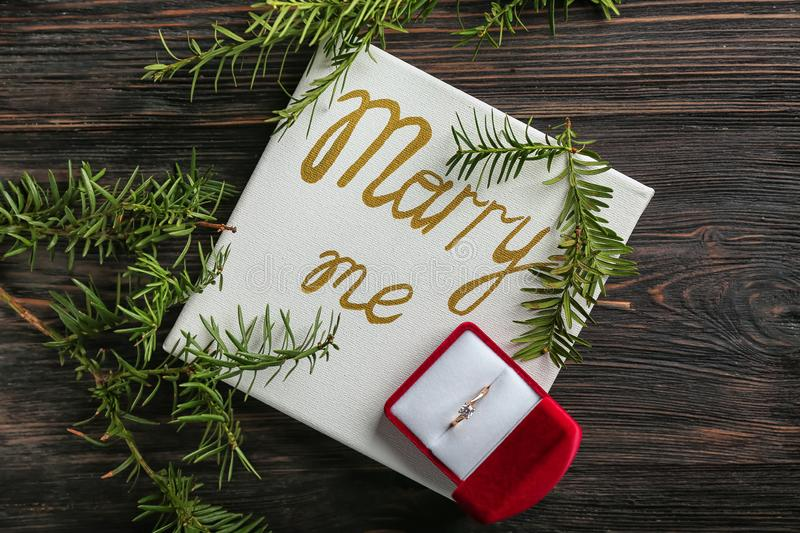 Beautiful engagement ring and paper with text MARRY ME on wooden table royalty free stock photo