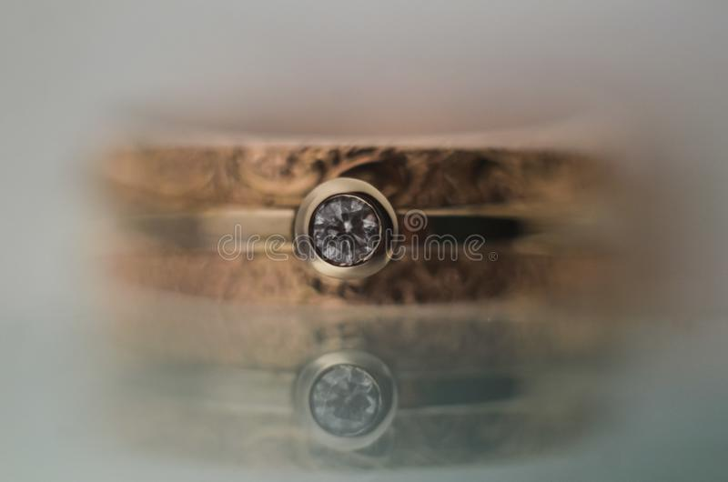 Beautiful engagement ring in white and yellow gold with a diamond on a glass surface with reflection. selective focus macro shot. royalty free stock images