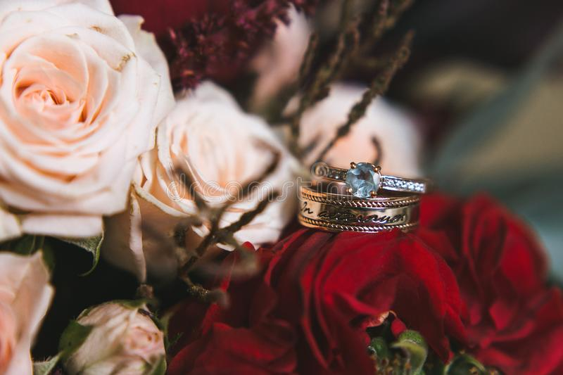 Beautiful engagement and wedding rings with topaz and diamonds on a bridal bouquet of white and red roses closeup royalty free stock photos