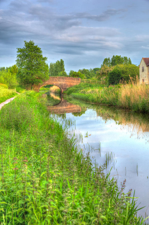 Beautiful English canal and bridge on calm still day in colourful HDR. Bridgwater and Taunton Canal Somerset UK peaceful waterway in the west country in HDR stock photo