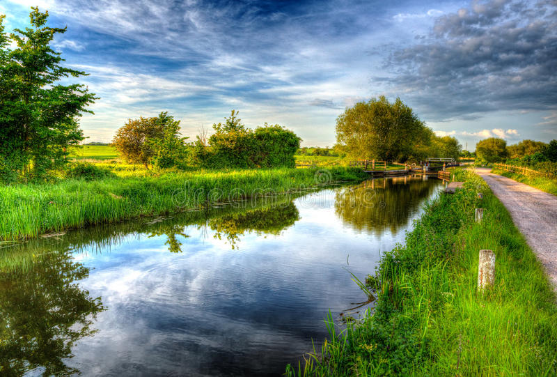 Beautiful English canal and lock gate on calm still day in colourful HDR. Bridgwater and Taunton Canal Somerset UK peaceful waterway in the west country in HDR stock photos