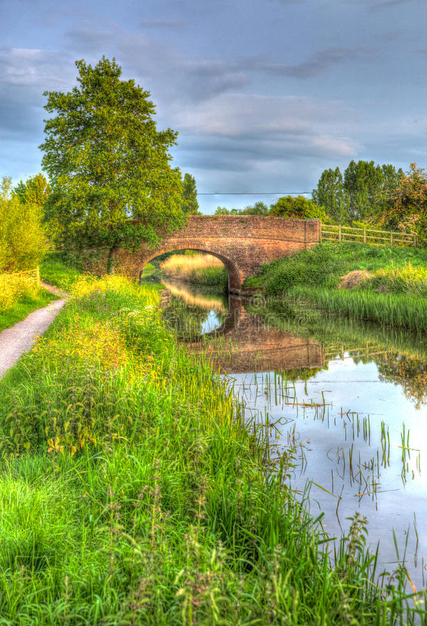Beautiful English river and bridge on calm still day in colourful HDR. Bridgwater and Taunton Canal Somerset UK peaceful waterway in the west country in HDR royalty free stock photo
