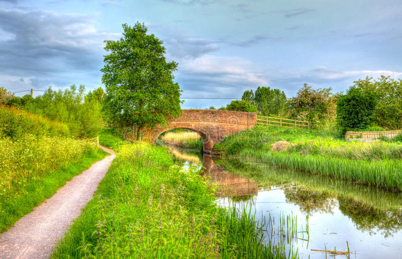 Beautiful English river and bridge on calm still day in colourful HDR. Bridgwater and Taunton Canal Somerset UK peaceful waterway in the west country in HDR stock photography