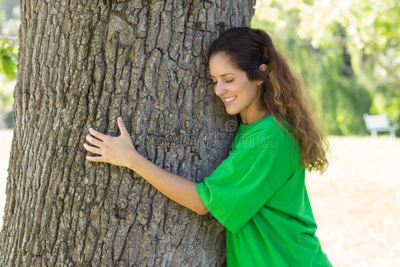 Beautiful environmentalist embracing tree trunk. Beautiful young environmentalist embracing tree trunk in park stock photos