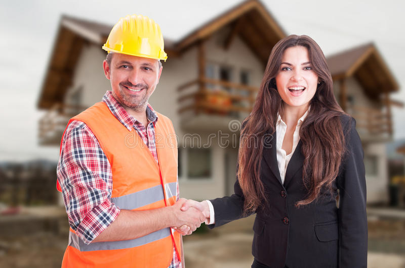 Beautiful estate agent handshake with construction male royalty free stock photos