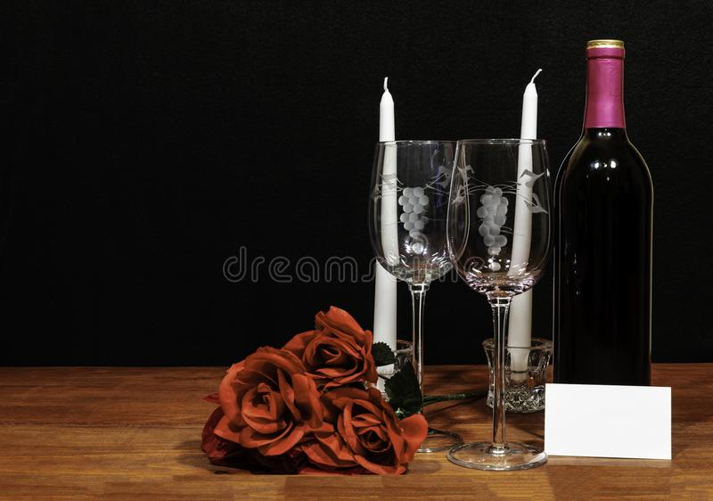 Beautiful etched wine glasses and bottle of red wine, white candles and red roses on wooden table with name tag on dark background stock photos