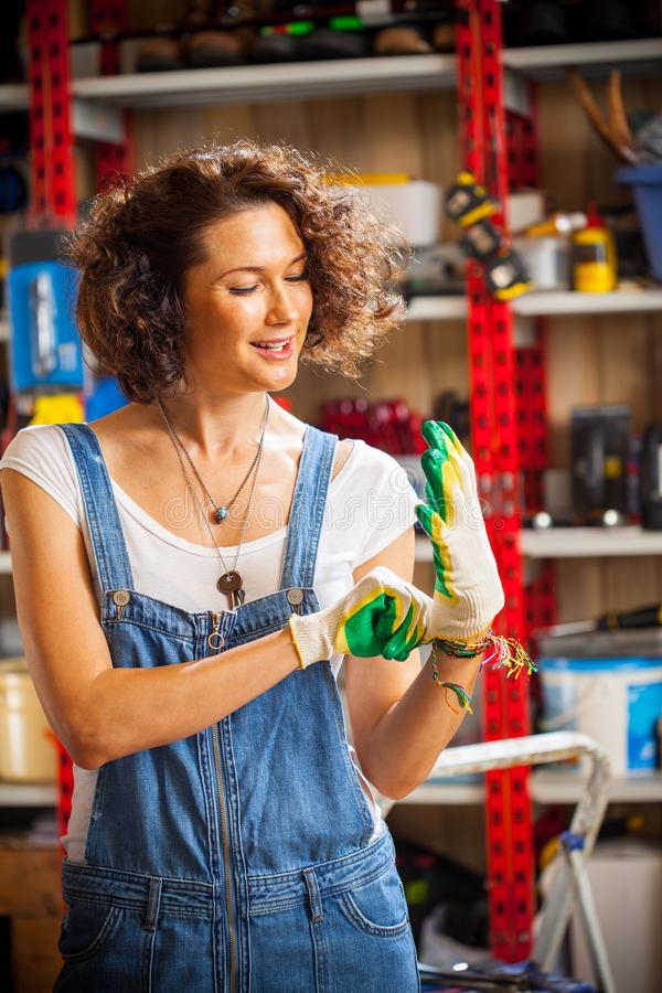 Beautiful woman mechanic wearing protective gloves royalty free stock image