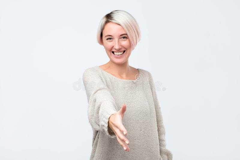 Beautiful european woman stretches hand in front, greets somebody, being glad to meet with friend. I am glad to see you, first meet with your coworker stock image