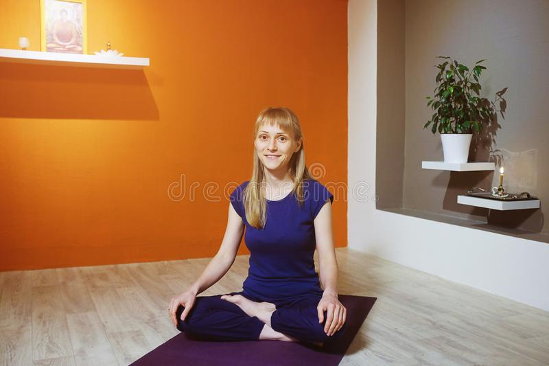 Beautiful European young woman sitting in Lotus position on purple yoga Mat, indoors, looking at camera and smiling. Time for yoga royalty free stock image
