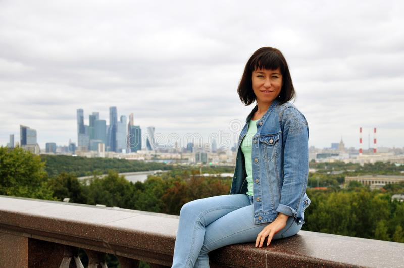 Beautiful European young woman traveler sits on the parapet and enjoys the views of Moscow. Vrorbievy Gory, view of the Moscow royalty free stock photos