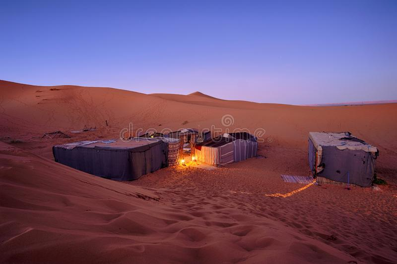 Touristic desert campsite with tents behind the sand dunes stock images