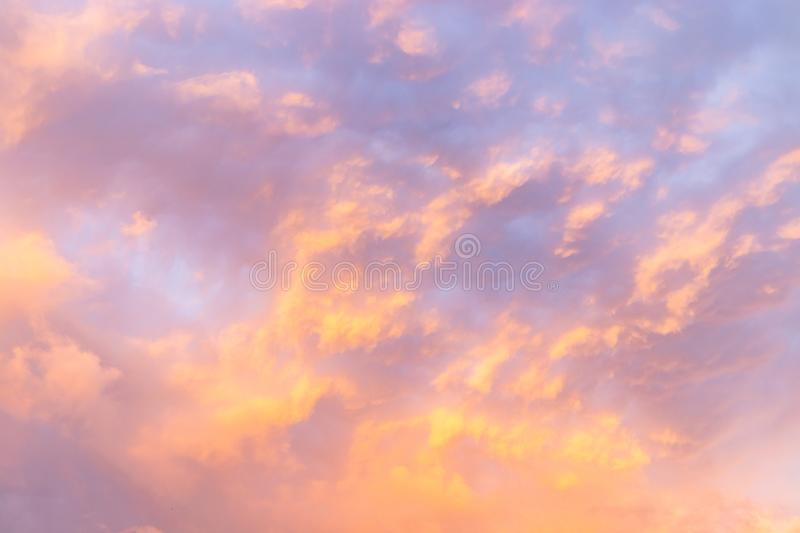 Beautiful evening cloudy sky with a small illuminated area. Pink warm clouds at sunset. Colorful background of evening clouds royalty free stock images