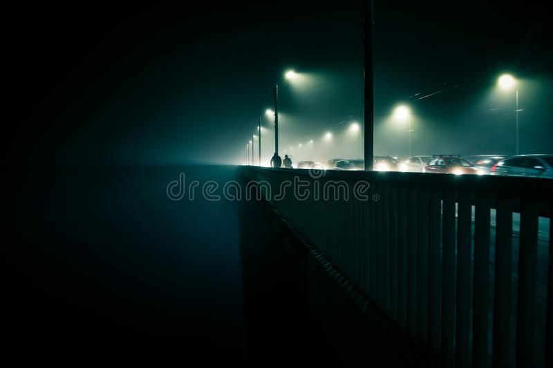 A beautiful evening fog above the river in city centre. Bridge in the mist, autumn scenery. Soft, blurry, misty look. Colorful, my stock image