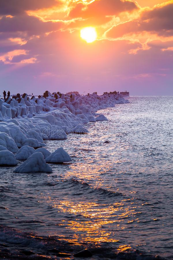 A beautiful evening landscape of a frozen breakwater in the Baltic sea. Winter landscape at the beach. stock photography