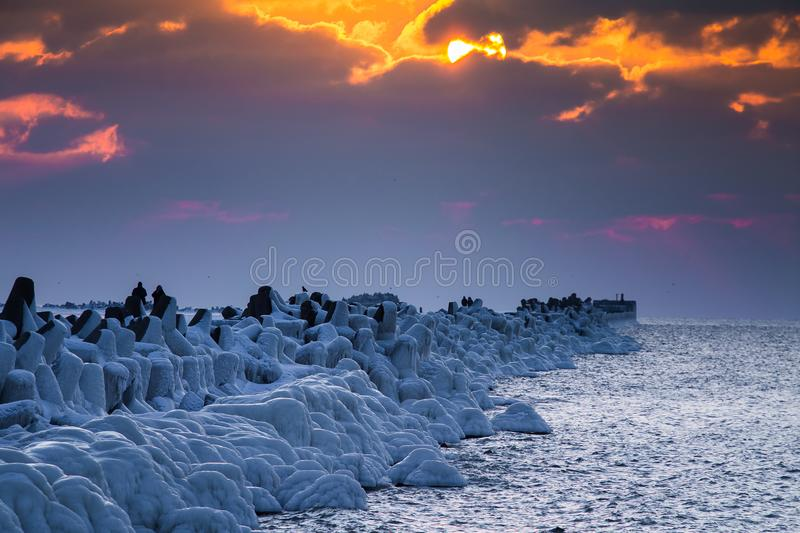 A beautiful evening landscape of a frozen breakwater in the Baltic sea. Winter landscape at the beach. royalty free stock photos