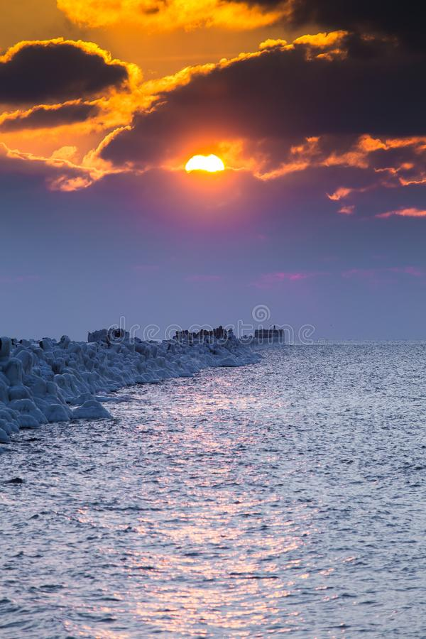 A beautiful evening landscape of a frozen breakwater in the Baltic sea. Winter landscape at the beach. royalty free stock images