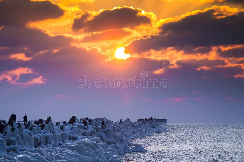 A beautiful evening landscape of a frozen breakwater in the Baltic sea. Winter landscape at the beach. stock photos