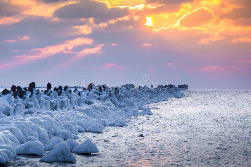 A beautiful evening landscape of a frozen breakwater in the Baltic sea. Winter landscape at the beach. stock image