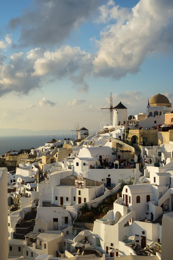 Beautiful evening light scene of Oia white building townscape and windmill along island mountain, Aegean sea, abstract cloud royalty free stock photos
