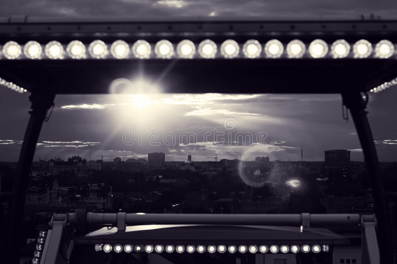 Beautiful evening sky. View from Ferris wheel towards city at sunset. Rays of sun filtering through clouds. Toned black and white photo royalty free stock image