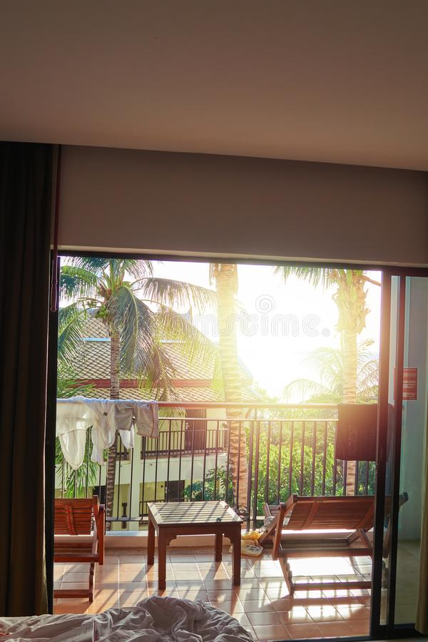 Beautiful evening sunshine shines in hotel room. Concept rest. Tropical resort bedroom, balcony with sun loungers. Beautiful evening sunshine shines in hotel stock photo