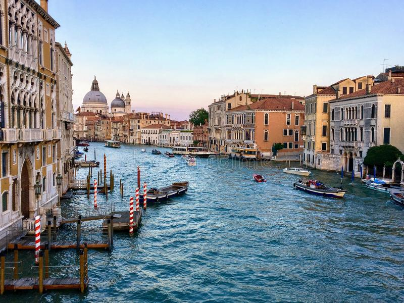 A beautiful evening view of the Grand Canal in Venice, Italy with water taxis and gondolas past by and the Santa Maria Della Salut. E in the background stock photo