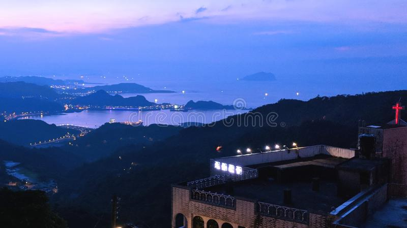 The sunset behind the mountains of Taiwan creates a purple backdrop against clear skies at dusk. On an overlook, watching sun set behind the mountains of Taiwan royalty free stock photos