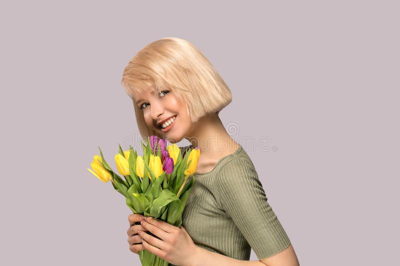 Woman holding a bouquet of tulips. Beautiful excited smiling woman holding a bouquet of tulips on gray background stock images