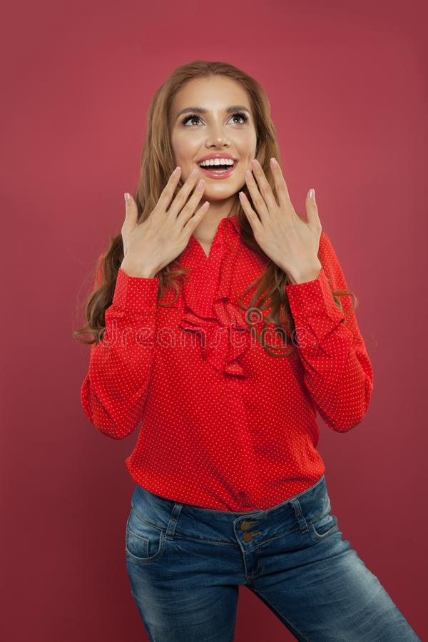 Beautiful excited surprised student girl portrait. Happy young woman with opened mouth on colorful bright pink background stock image