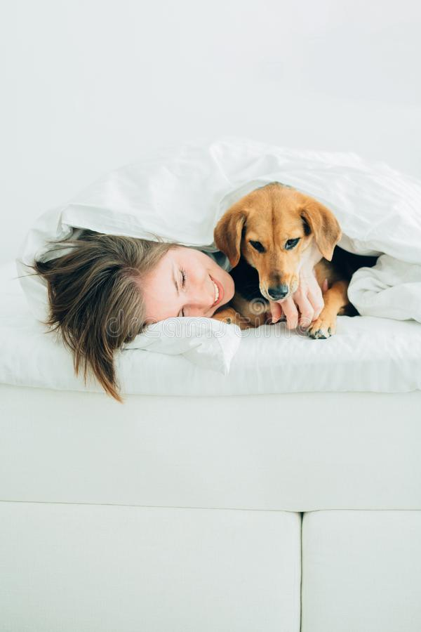 Beautiful excited young woman and her cute cur dog are fool around, looking at camera while lying covered with a blanket in bed. royalty free stock photo