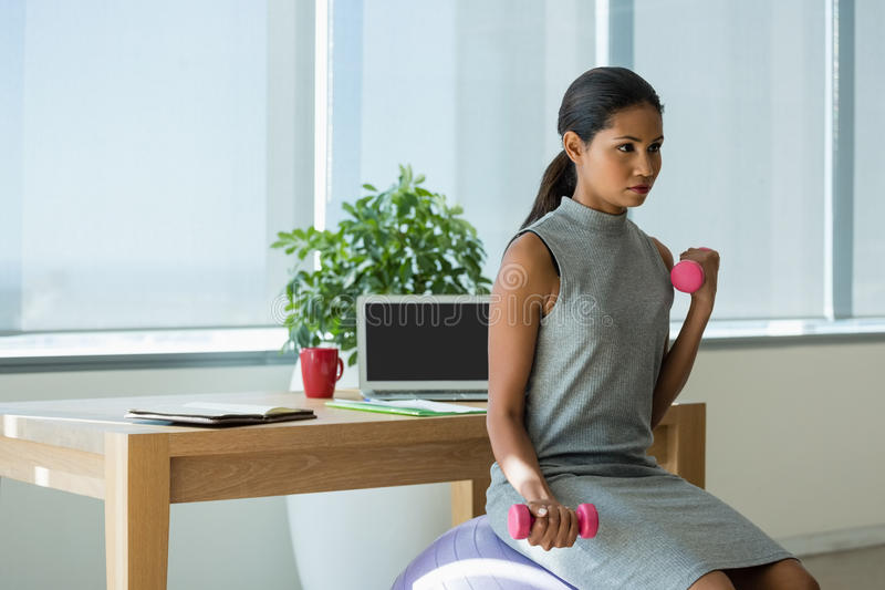 Beautiful executive lifting dumbbells while exercising on fitness ball. In office stock images